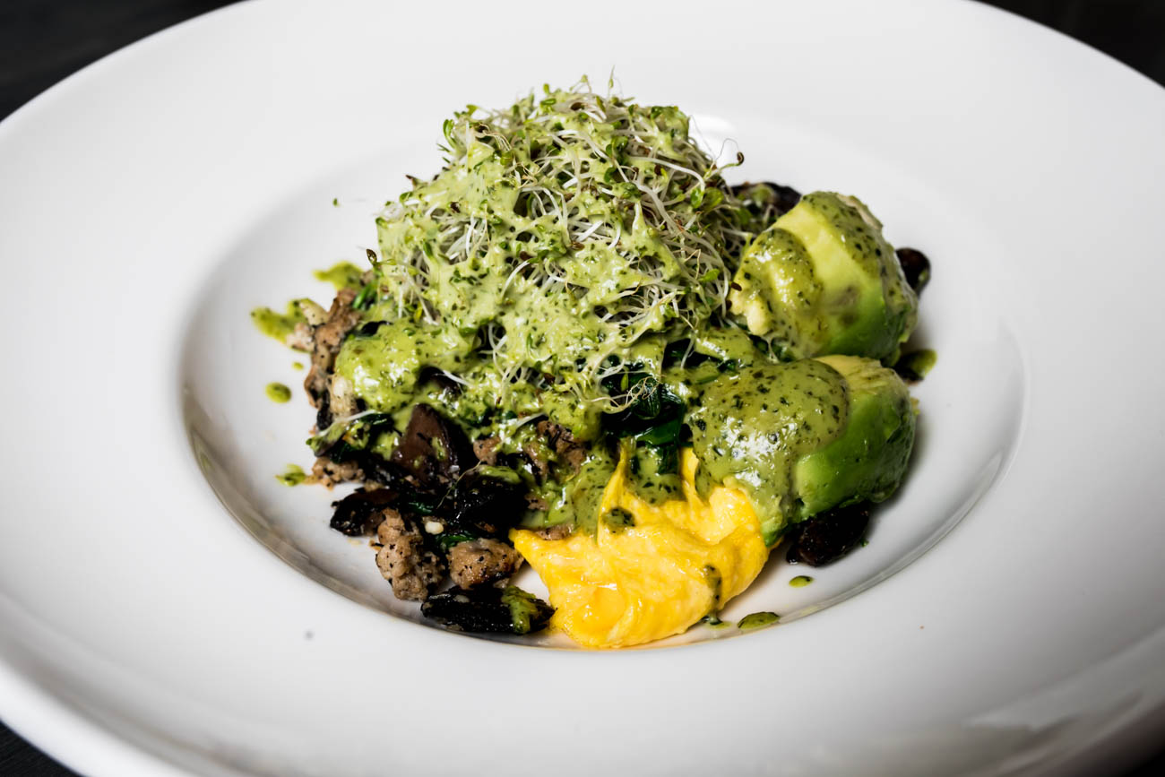 CBeeD Bowl: house-seasoned chicken sausage, sauteed power greens, mushrooms and garlic herbs served over two scrambled eggs. Topped with avocado and broccoli sprouts and dressed with chimichurri / Image: Amy Elisabeth Spasoff // Published: 3.4.18